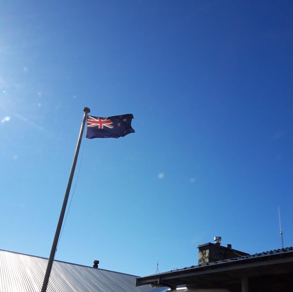 20191228_092511 (2)  - Neuseeland - Canterbury (NZ) - Mount Cook Village (NZ) - neuseeländische Fahne - kräftiger Wind - blauer himmel Sonne