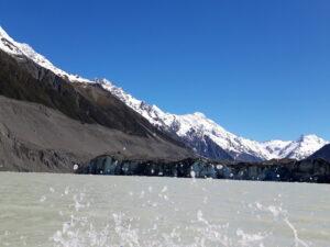 20191228_105016 - Neuseeland - Canterbury NZ - Mount Cook Village (NZ) - Aoraki/Mt. Cook (3.724M) - Moräne - Bootsfahrt - Zodiac - Tasman Lake See - Tasman Gletscher - blauer Himmel - aufspritzendes Wasser
