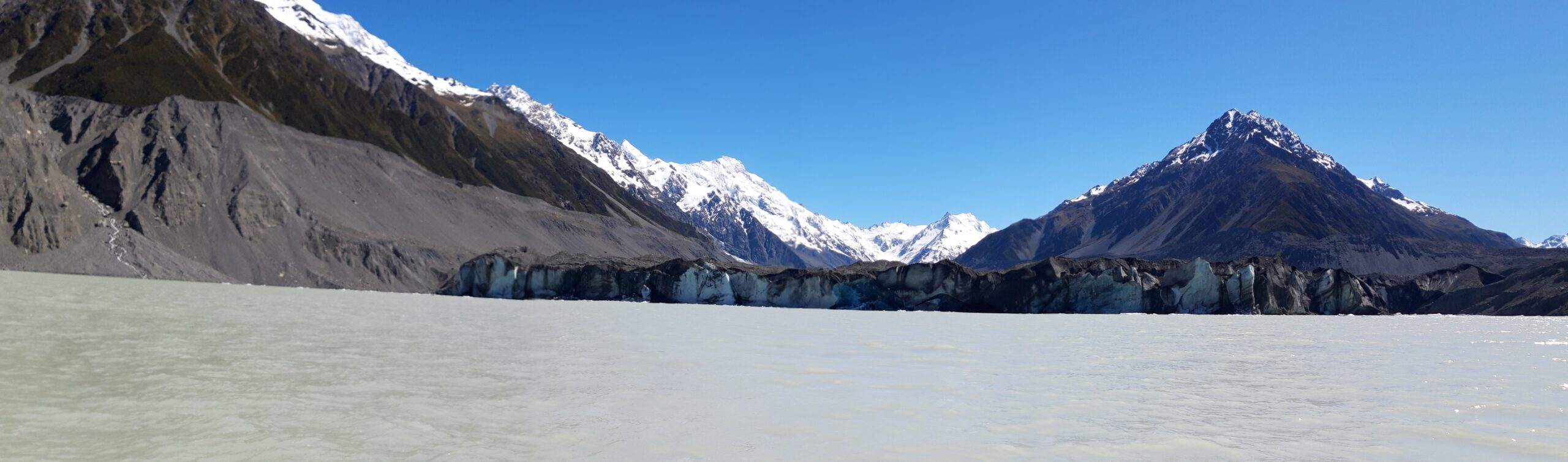20191228_105317 - Neuseeland - Canterbury NZ - Mount Cook Village (NZ) - Aoraki/Mt. Cook (3.724M) - Mt. Tasman - Mt. Graham - Novara Peak - Bootsfahrt - Zodiac - Tasman Lake See - Tasman Gletscher - blauer Himmel - Eisberg